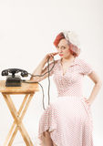 Redhead woman with a retro look waiting for the phone Royalty Free Stock Photos