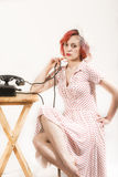 Redhead woman with a retro look waiting for the phone Stock Photo
