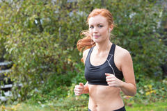Redhead woman running outsdie on a trail Stock Images