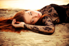 Redhead woman on sand. Redhead beautiful woman on sand by the river Stock Photos
