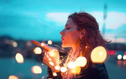 Redhead woman sending kiss with fairy light garland at evening. Outdoors royalty free stock photo