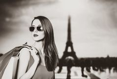 Redhead woman with shopping bags. On parisian background stock photo