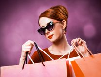 Redhead woman with shopping bags. On purple background stock image
