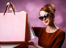 Redhead woman with shopping bags. On purple background stock photos