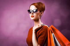 Redhead woman with shopping bags. On purple background royalty free stock photography