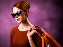 Redhead woman with shopping bags. On purple background royalty free stock images