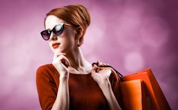 Redhead woman with shopping bags. On purple background stock photo