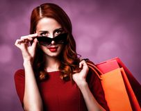 Redhead woman with shopping bags. Redhead woman in sunglasses with shopping bags on purple background stock photos