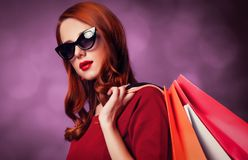 Redhead woman with shopping bags. Redhead woman in sunglasses with shopping bags on purple background stock images