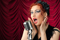 Redhead woman singing into vintage microphone Royalty Free Stock Photography