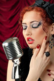 Redhead woman singing into vintage microphone Stock Images