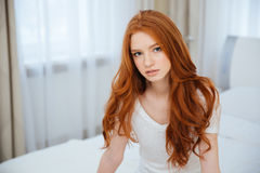 Redhead woman sitting on the bed at home Royalty Free Stock Photography