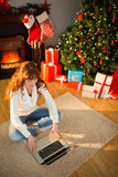 Redhead woman sitting on floor using laptop at christmas Stock Images