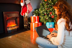 Redhead woman sitting on floor using laptop at christmas Royalty Free Stock Photos