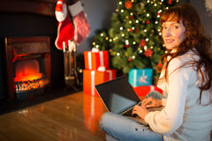 Redhead woman sitting on floor using laptop at christmas Stock Photography