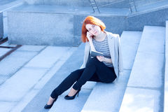 Redhead woman sitting outside on the stairs with tablet Royalty Free Stock Photos