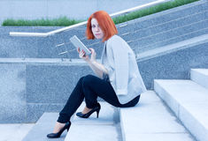 Redhead woman sitting outside on the stairs with tablet Stock Photo
