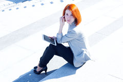 Redhead woman sitting on the street on the stairs with tablet Royalty Free Stock Photography