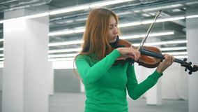 Redhead woman is skillfully playing the violin in an empty hall. 4K stock video footage