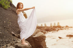 Redhead woman standing on the coast on beach. Redhead woman standing on the coast on beach and looks into the distance at sea. Selective soft focus Royalty Free Stock Image