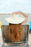 Redhead Woman In Straw Hat On Deck Chair. Rear view of a redhead woman in straw hat sitting on deck chair at roof terrace Stock Photos