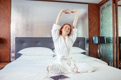 Redhead Woman stretching in bed after waking up. Entering a day happy and relaxed after good night sleep Stock Image