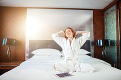Redhead Woman stretching in bed after waking up. Entering a day happy and relaxed after good night sleep Royalty Free Stock Photo