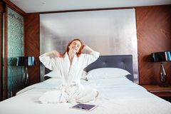 Redhead Woman stretching in bed after waking up. Entering a day happy and relaxed after good night sleep Royalty Free Stock Images