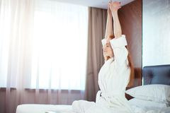 Redhead Woman stretching in bed after waking up. Entering a day happy and relaxed after good night sleep Stock Photos