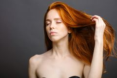 Redhead woman holding her healthy and shiny hair, studio grey. Redhead woman with strong healthy hair portrait. ginger girl shows natural hair strength Royalty Free Stock Photos