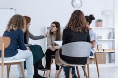 Redhead woman supporting friend during psychotherapy group meeting stock photo