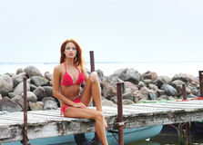 A redhead woman in a swimsuit sitting on a dock Stock Photography