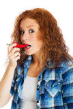 Redhead woman taking bite of spicy red pepper Stock Images