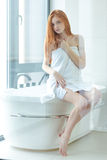 Redhead woman in towel sitting on bathroom. Full length portrait of a young redhead woman in towel sitting on bathroom Royalty Free Stock Photos