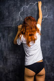 Redhead woman in underwear drawing on a blackboard. Redhead woman in her underwear drawing on a blackboard Stock Photos