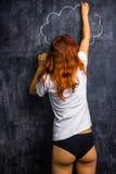 Redhead woman in underwear drawing on a blackboard Stock Photos
