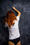 Redhead woman in underwear drawing on a blackboard Stock Images