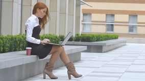 Redhead woman using laptop with a cup of coffee on the terrace stock video