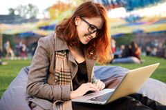 Redhead woman using laptop in the park lying on the green grass. Stock Photography