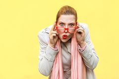 Redhead woman wearing coat, opening mouths widely, having surprised shocked looks. stock photos
