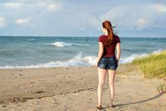 Redhead woman wearing shorts walking on beach Royalty Free Stock Photography