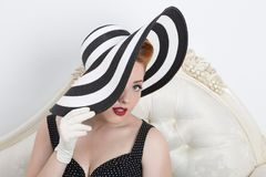 Redhead woman holding a striped hat Stock Photos