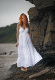 Redhead woman in white dress. Beautiful redhead woman in white dress goes along the coast royalty free stock images