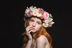 Redhead woman with wreath from flowers on head. Beauty portrait of a young redhead woman with wreath from flowers on head looking at camera over black background stock photography