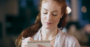 Redhead woman writing on notepad portrait.Corporate business team work office meeting.Caucasian businessman and stock video