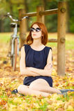 Redhead women near bike Royalty Free Stock Photo