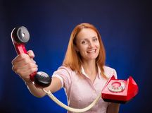 Redhead women with red telephone. Stock Photography