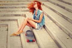 Redhead women sitting on a stairs  with her skateboard in sunglasses Stock Images