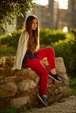 Redhead 12 years old girl sitting on a rock and busy thinking. Wearing white shirt, red pants and black shose Royalty Free Stock Image