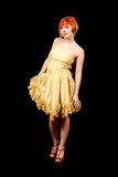 Redhead in yellow dress. Beautiful Caucasian redhead woman in yellow cocktail dress standing tilted, isolated royalty free stock photo